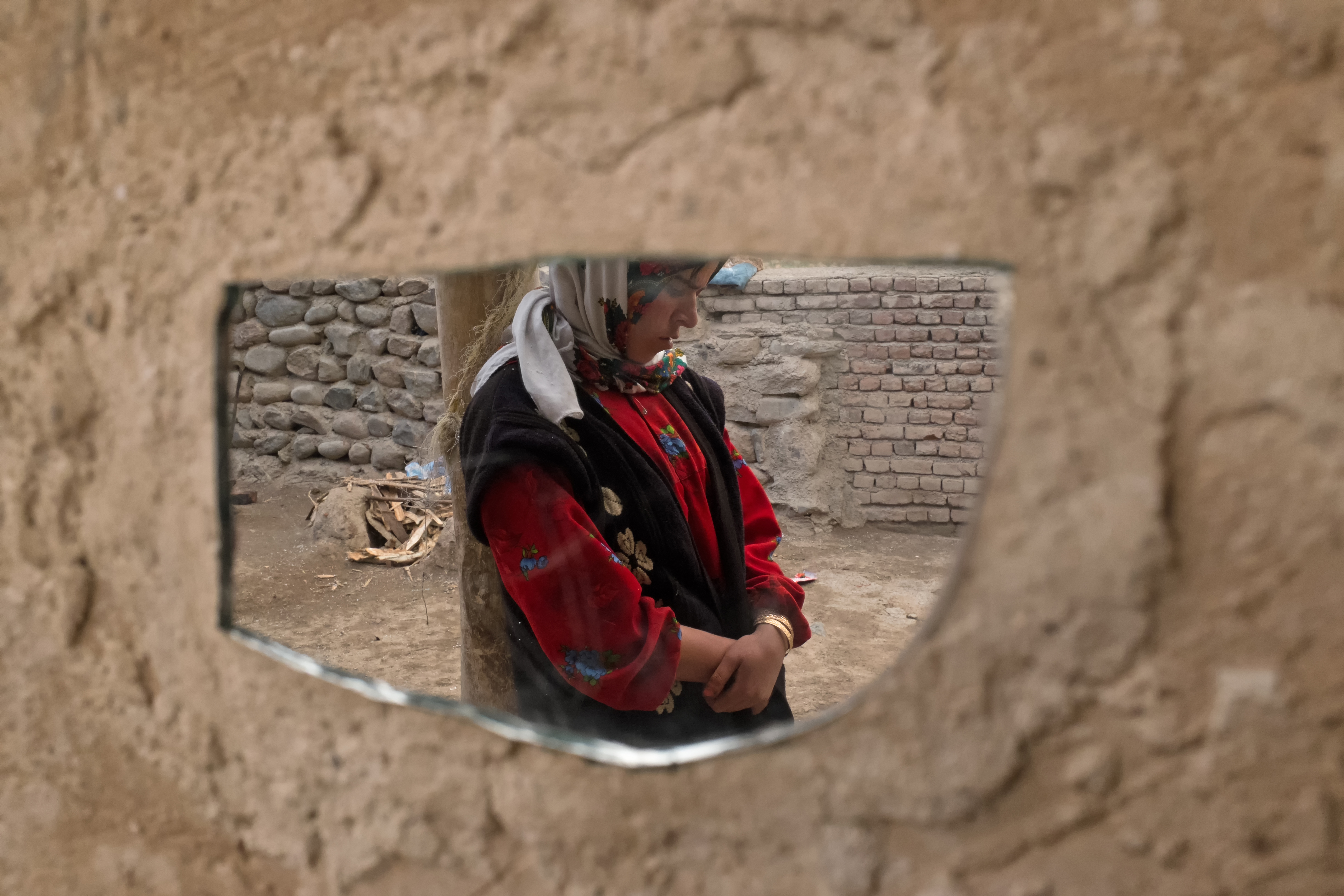 Roghayyeh leaning against a wodden pole and absorbed in her thoughts is reflected in a mirror on the mud wall. By losing her virginity she also lost hope for her future. Ajabshir, East Azerbaijan, Iran.