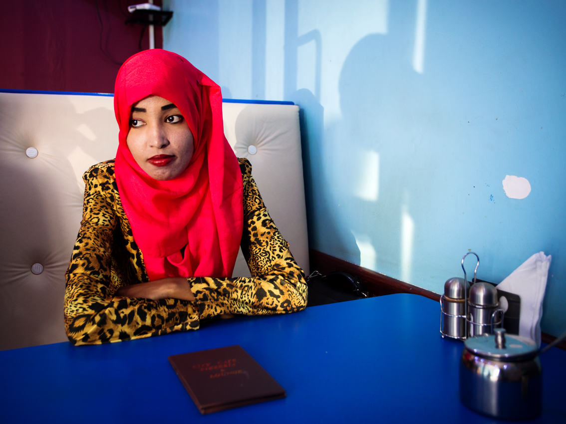 Bishara, 20, a refugee from Somalia and a student of journalism in Kampala is sitting for a portrait in a small coffeshop in Kisenyi, Kampala.