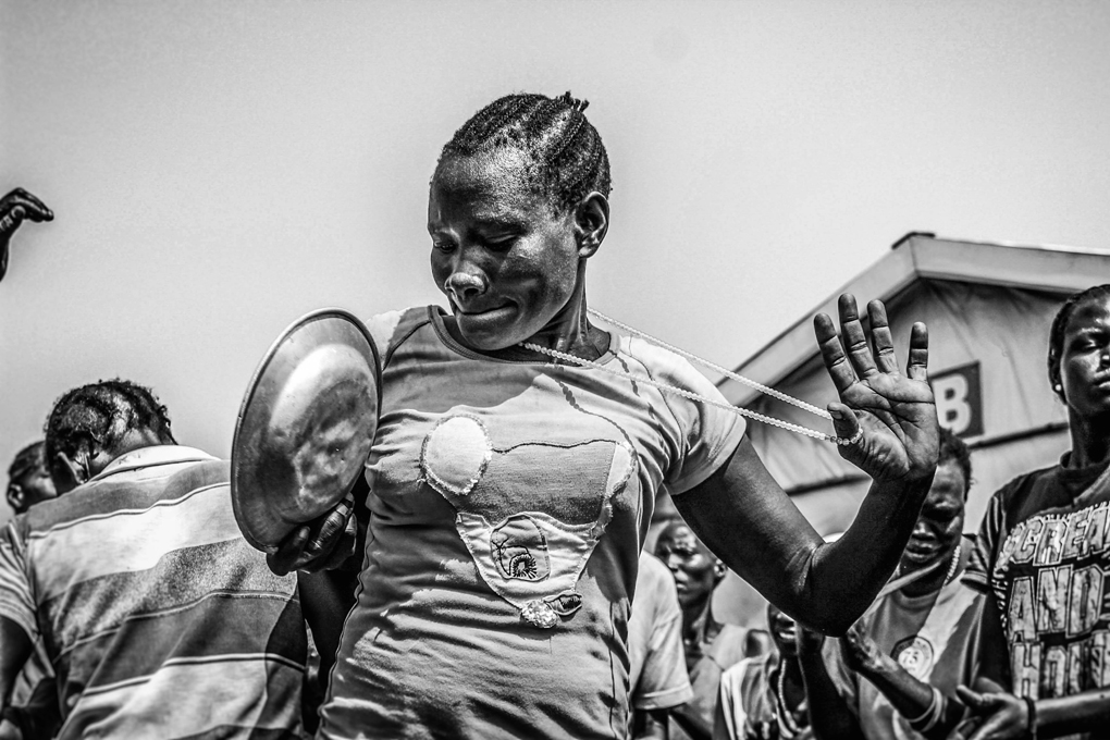 A South Sudanese refugee woman in Nyumanzie transit centre shows off traditional dance. More than 80% of the refugee population in Uganda are women and children.