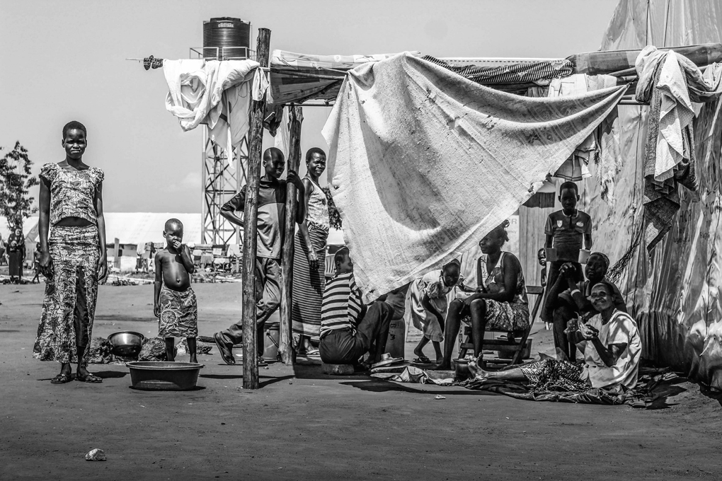 A group of refugees seek shelter from the sun at Nyumanzie transit centre. The war in South Sudan is forcing thousands of people out of the country into neighbouring Uganda, DRC and Kenya. Due to Uganda's lenient refugee policy, many choose to travel here and settle indefinitely.