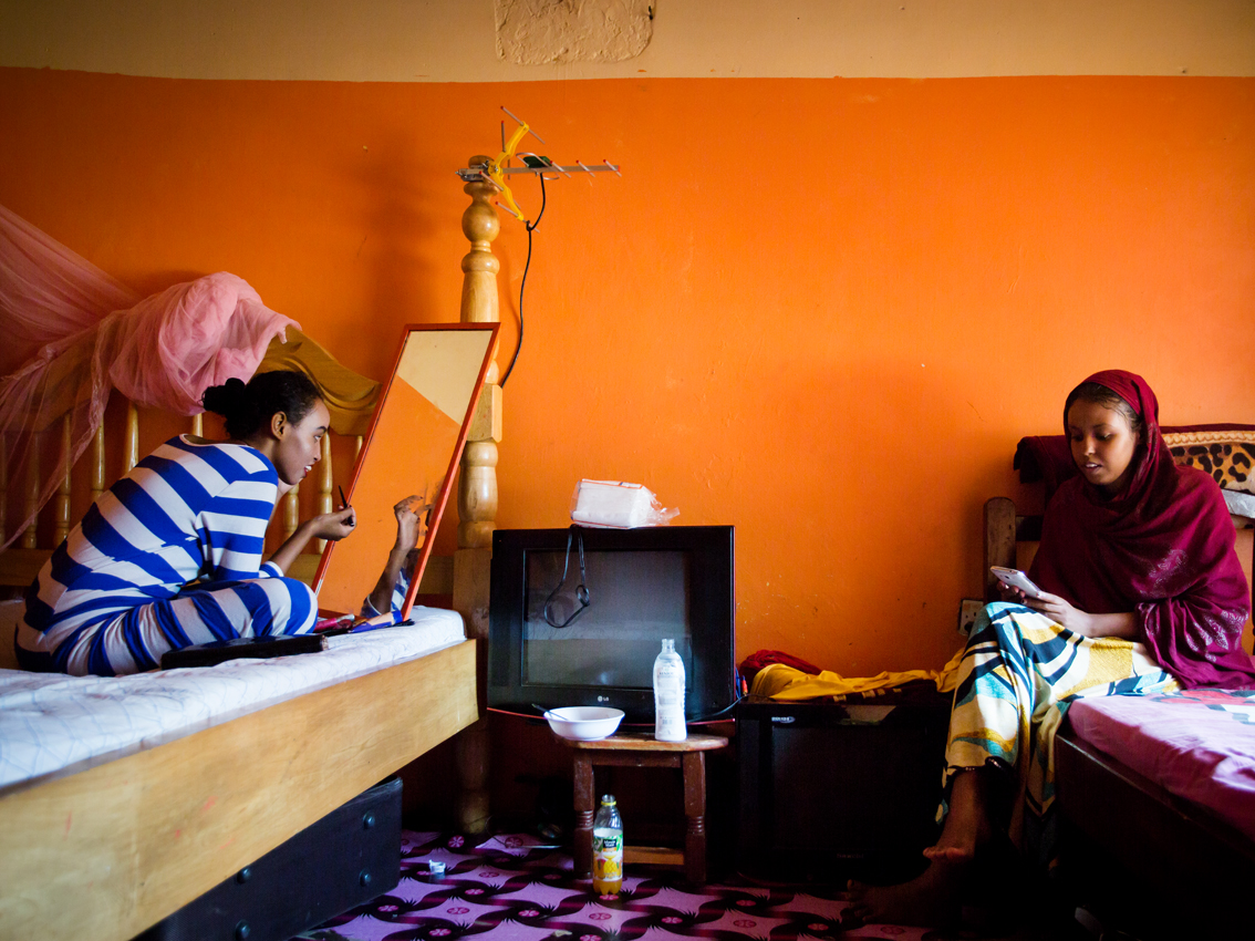 "Bishara (left), 20, is seen in a home setting without wearing her veil and while putting on makeup to go out. On the opposite bed sits her younger sister Amal, with whom, amongst others she shares this room. Bishara is studying and working at the same time. She lives in a female only household in Kisenyi, Kampala's neighbourhood nicknamed "" Little Mogadishu"" for its high number of Somali migrants, headed by her grandmother, sharing a small space with her mom, aunts and four sisters."