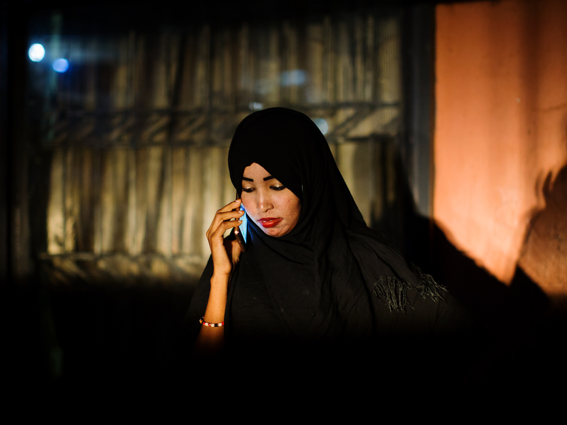 Bishara is calling her Somali boyfriend in Berlin outside of her family's appartment in Kisenyi. He wants to marry her eventually and live with her in Germany. They have not seen for over a year, but keep in touch through phone and internet.