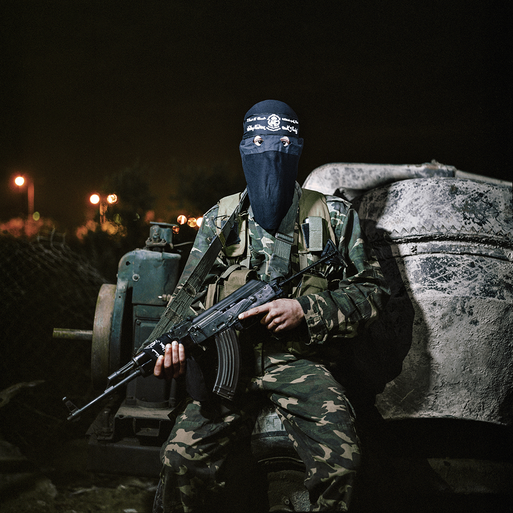 """Usama poses for a picture after an evening training drill. He is a member of the Nasser brigades, one of various Palestinian militant organisations which operates in the Gaza strip. When asked about his future dreams and aspirations he says: """" That all my land comes back to the Palestinian people. And to go to Jerusalem. I want it so bad"""".Gaza strip, Palestinian territories. November 2012."""